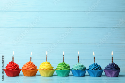 фотография Delicious birthday cupcakes with burning candles on blue wooden table