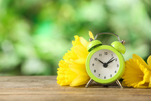 Alarm Clock And Beautiful Spring Flowers On Wooden Table, Space For Text. Time Change Concept