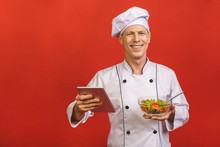 Picture Of Happy Young Senior Chief Cook In Uniform Standing Isolated Over Red Wall Background, Holding Salad And Tablet Computer.