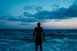 African American male standing near the sea under a blue cloudy sky shot from behind