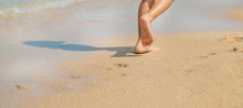 Child Walks Along The Beach Leaving Footprints In The Sand. Selective Focus.