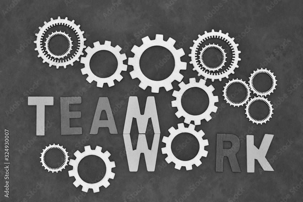 Fototapeta Trabajo en equipo, escrito en inglés, con ruedas de engranaje y letras de madera
