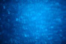 Blue Puzzle Shape Bokeh. Defocused Background For Autism Awareness Day. Real Photo. Light Blue