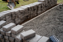 Laying Gray Concrete Paving Slabs Along A House Walkway. Stacks Of Concrete Blocks Are Prepared To Be Layed On Walk Or Patio On Gravel Foundation Base.