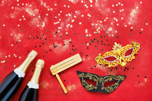 Two Champagne Bottles, Carnival Mask And Gragger On Red Background. Flat Lay Of Purim Carnival Celebration Concept.