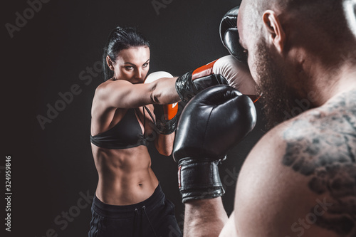 Stampa su Tela Shirtless Woman exercising with trainer at boxing and self defense lesson, studio, dark background