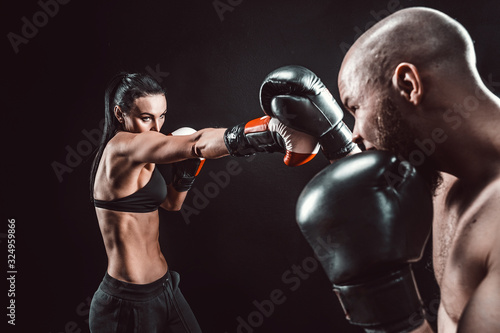 Cuadros en Lienzo Shirtless Woman exercising with trainer at boxing and self defense lesson, studio, dark background