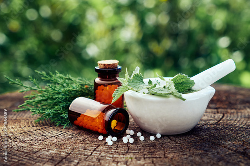 Photo Bottle of homeopathic globules, mortar of green nettle and mint leaves, juniper twigs