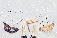 Two Champagne Bottles, Carnival Mask And Gragger On Light Background. Flat Lay Of Purim Carnival Celebration Concept.