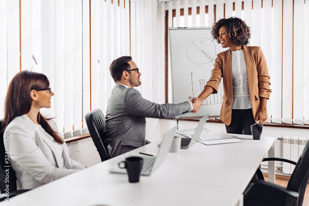 Fototapeta Cheerful businesswoman handshake with a colleague at the meeting
