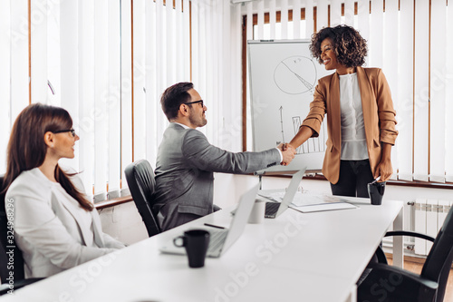 Obraz Cheerful businesswoman handshake with a colleague at the meeting - fototapety do salonu