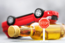 Road Sign, A Bottle Of Whiskey And An Inverted Car. Concept On The Topic Of Drunk Driving