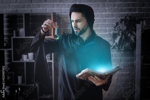 Fototapeta Male alchemist with spell book and elixir in laboratory obraz