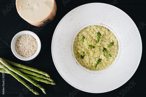Risotto with asparagus in white plate on a black wooden table Canvas Print