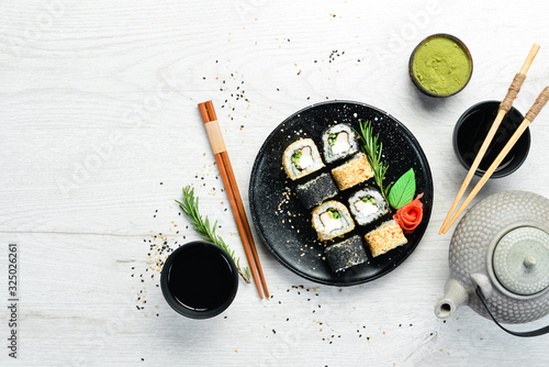 Fototapeta Traditional Sushi - Black and White, with crab, cheese and herbs. Japanese cuisine. Top view. obraz