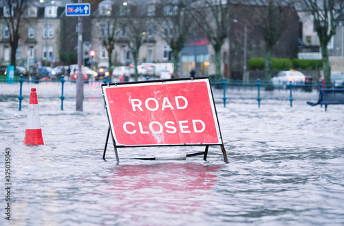 Fotografía Road flood closed sign under deep water during bad extreme heavy rain storm weat