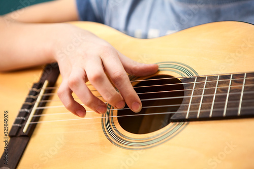 Fotografija Female hand plucks the strings of a yellow acoustic guitar, close up view