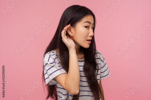Photo What? I can't hear! Portrait of curious girl with long brunette hair in striped t-shirt holding palm near ear and listening carefully, hearing problems