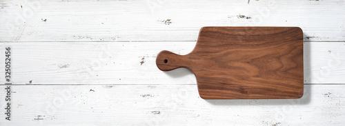 Fotografía Handmade walnut wood cutting board on white wooden board desktop.