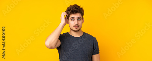 Fototapeta Young caucasian man isolated background with an expression of frustration and not understanding obraz