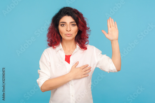 Photo I swear! Portrait of hipster woman with fancy red hair holding hand on heart and raising palm to make oath, devoting herself, promising to fulfill task responsibly