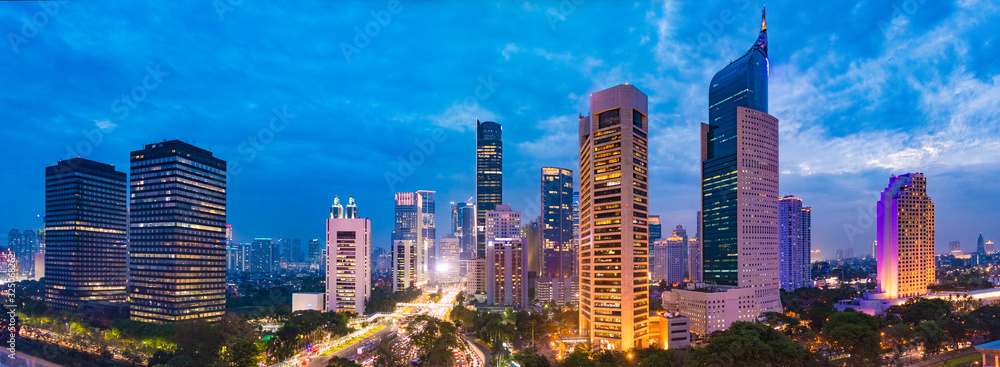 Fototapeta Aerial view of Jakarta's Central Business District at dusk (blue hour). Jakarta cityscape at sunset. A panorama stitched from 3 photos. Jakarta cityscape. Widescreen photo.