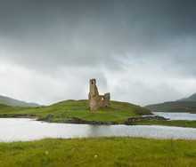 Landscape With Ancient Ruins Of The Small Castle Of Ardvreck In Scotland On A Lake And With Cloudy Skies.
