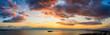 Weites Aerial Panorama eines bewölkten Sonnenunterganges über dem Meer mit von der Sonne rot angestrahlten Wolken