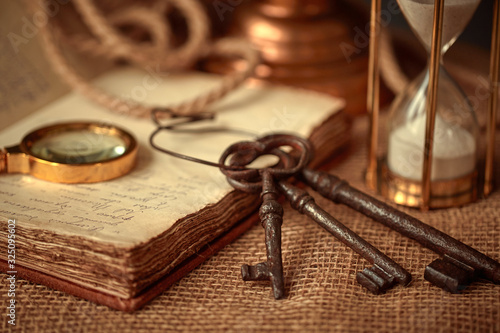 Photo Old vintage items of the treasure hunter, traveler and discoverer - a magnifying glass, old manuscripts, a globe, keys to chests