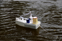 A Homemade, Toy Ship With A Gun In The Water. The Boat Is Drifting In The Pond