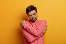 Peaceful Bearded Man Crosses Hands Over Body, Feels Comfort In His New Sweater, Expresses Self Love, Tilts Head And Closes Eyes, Warms Up Himself, Isolated On Yellow Wall, Thinks About Something Good