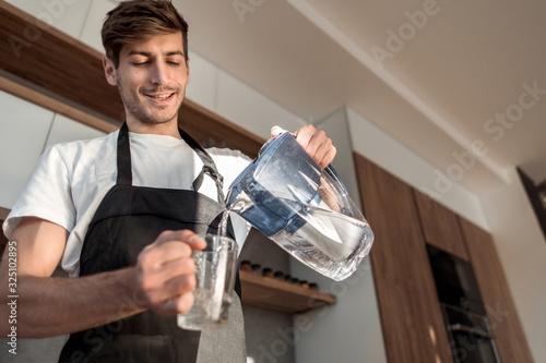 Carta da parati young man pours clean water into a glass