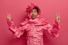 Surprised Funny Man Has Fun In Office, Poses In Creative Costume Made Of Sticky Notes, Raises Fingers In Victory Gesture, Shows Peace Sign, Isolated Over Pink Background. Paper Outfit. Monochrome