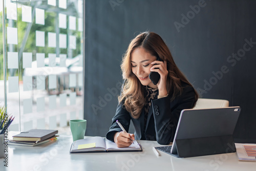 Foto Happy young asian woman talking on the mobile phone and smiling while sitting at her working place in office
