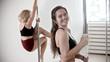 Two women having a pole dancing training in the white studio