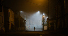 Lonely Woman Walking In A Foggy Old City In City Street Lights