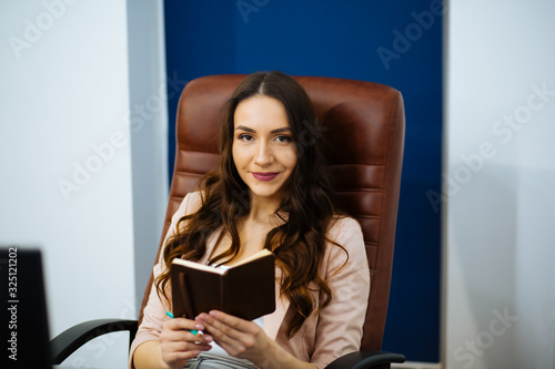 Fotografie, Tablou beautiful business woman dark-haired boss with long wavy healthy hair sitting at