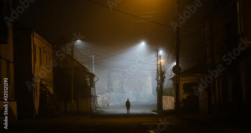 Fototapeta Lonely woman walking in a foggy old city in city street lights obraz