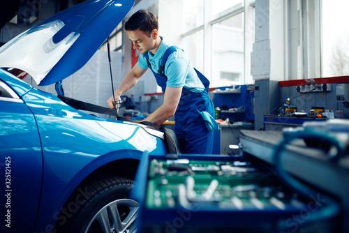 Worker in uniform checks engine, car service - 325121425