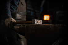 Glowing Hammer On The Anvil In Workshop - A Man Worker Standing On The Background