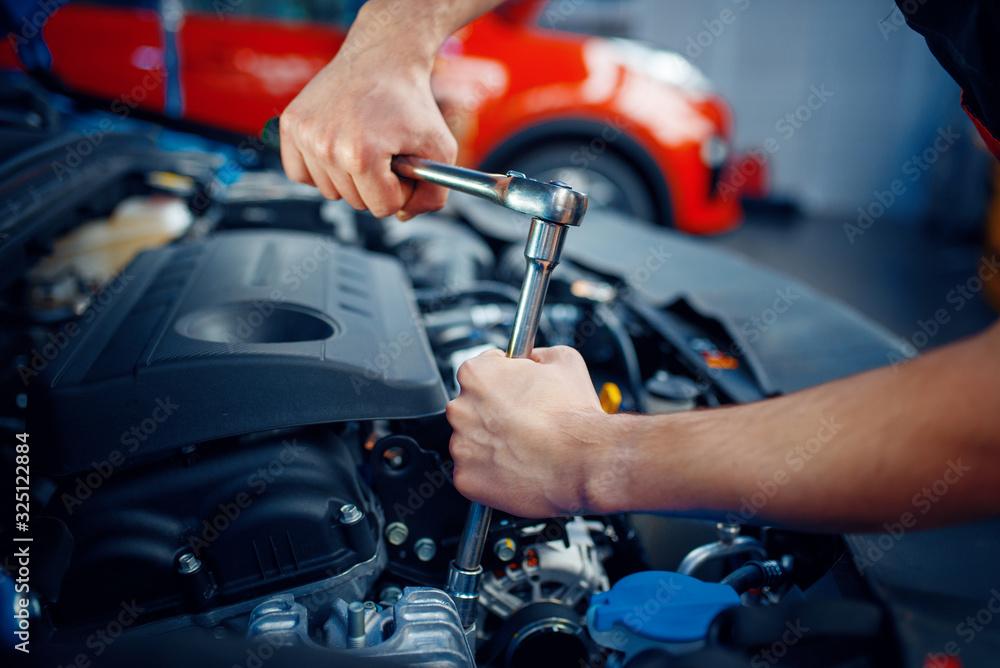 Fototapeta Worker disassembles vehicle engine, car service