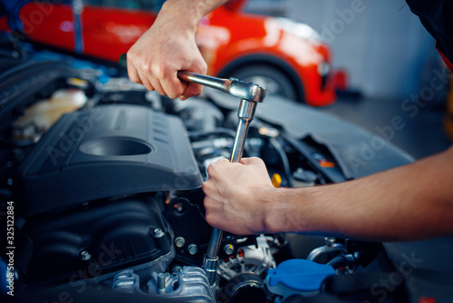 Valokuva Worker disassembles vehicle engine, car service