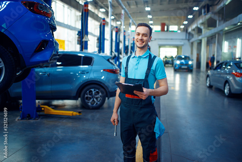 Repairman with a checklist, car service station