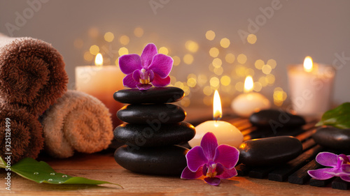 Photo Spa, beauty treatment and wellness background with massage stone, orchid flowers, towels and burning candles