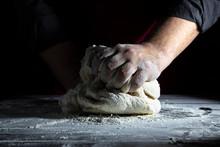 Male Chef Kneads Dough On A Wo...
