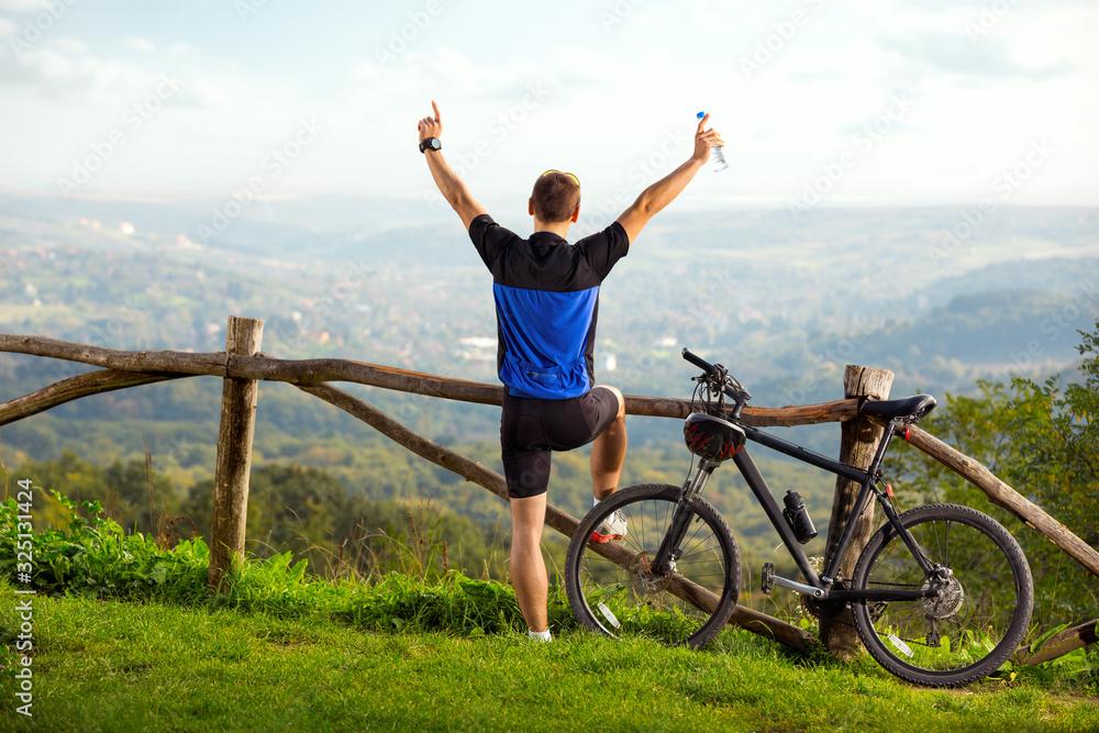Fototapeta happy man biker raised hands up in joy