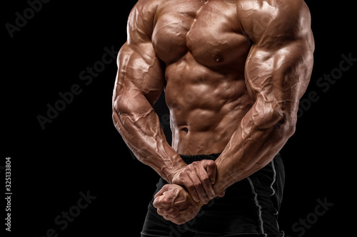 Muscular man showing muscles isolated on black background Fototapet