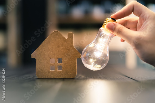 Light bulb with wood house on the table, a symbol for construction, Creative light bulb idea, power energy or business idea concept ecology, loan, mortgage, property or home Canvas Print