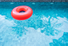 Red Pool Float, Ring Floating In A Refreshing Blue Swimming Pool With Shadow Of Coconut Tree. Copy Space, Summer Vacation Concept.