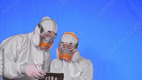 Scientist virologist in respirator makes write in an tablet computer with stylus Canvas Print